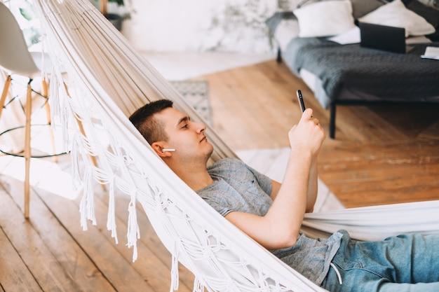 Un jeune homme d'affaires dans des écouteurs à l'aide de smartphone, navigue sur internet en position couchée dans un hamac au bureau à domicile
