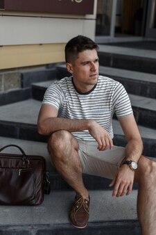 Jeune homme d'affaires dans un élégant t-shirt rayé d'été en short à la mode en chaussures en daim avec un sac en cuir se trouve sur un escalier en pierre vintage