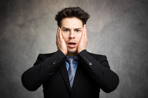 Jeune homme d'affaires dans une expression choquée