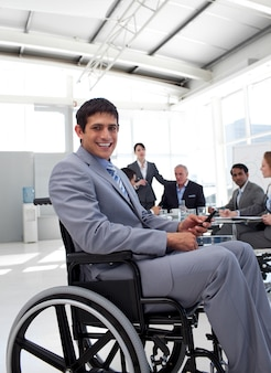 Jeune homme d'affaires dans un fauteuil roulant lors d'une réunion