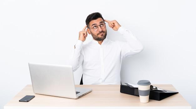 Jeune homme d'affaires dans un lieu de travail ayant des doutes et de la pensée