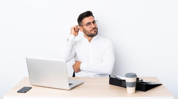 Jeune homme d'affaires dans un lieu de travail ayant des doutes