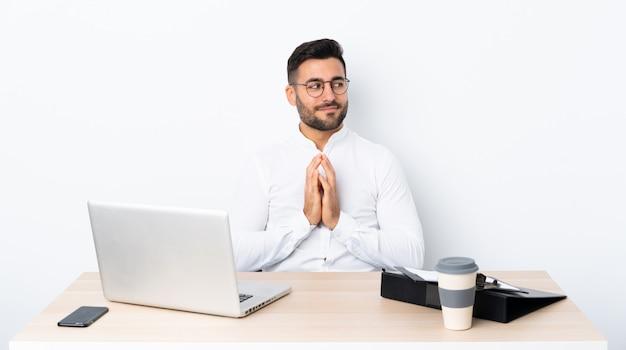 Jeune homme d'affaires dans un lieu de travail complotant quelque chose