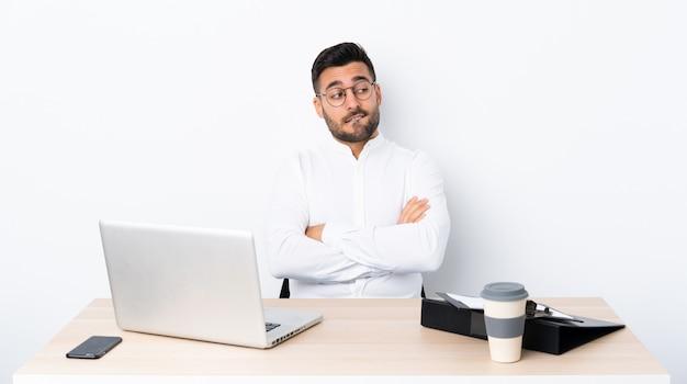 Jeune homme d'affaires dans un lieu de travail avec une expression de visage confuse