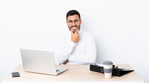 Jeune homme d'affaires dans un lieu de travail avec des lunettes et souriant