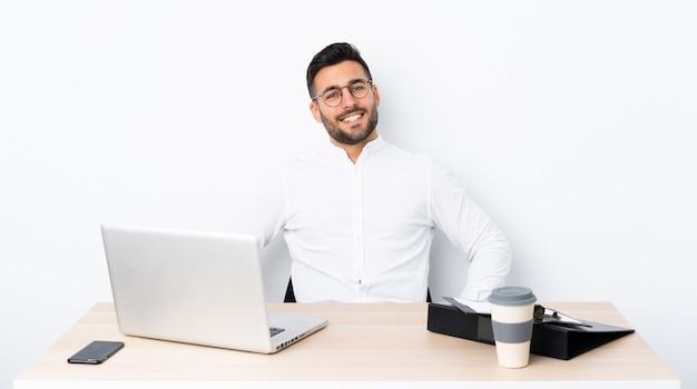 Jeune homme d'affaires dans un lieu de travail posant avec les bras à la hanche et souriant