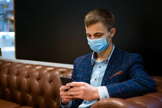 Jeune homme d'affaires dans un masque médical assis sur le canapé avec un téléphone dans sa main la lecture