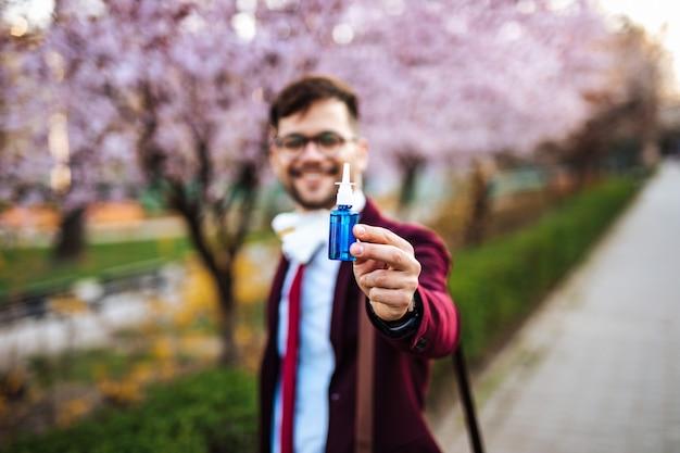 Jeune homme d'affaires dans le parc tenant des gouttes nasales. allergie, grippe, concept de virus.