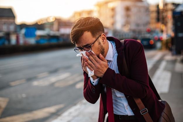 Jeune homme d'affaires dans la rue éternuant et attendant un bus ou un taxi. concept de pandémie de virus ou de pollution.