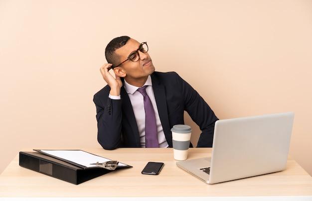 Jeune homme d'affaires dans son bureau avec un ordinateur portable et d'autres documents ayant des doutes