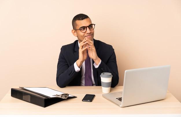 Jeune homme d'affaires dans son bureau avec un ordinateur portable et d'autres documents complotant quelque chose