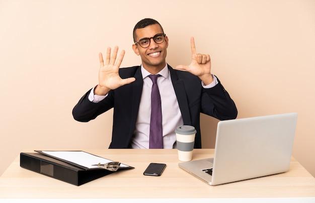 Jeune homme d'affaires dans son bureau avec un ordinateur portable et d'autres documents comptant sept avec les doigts
