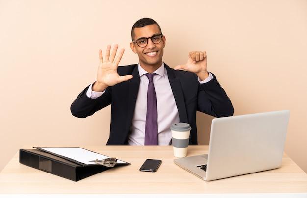 Jeune homme d'affaires dans son bureau avec un ordinateur portable et d'autres documents comptant six avec les doigts