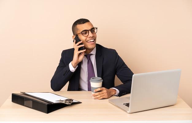 Jeune homme d'affaires dans son bureau avec un ordinateur portable et d'autres documents contenant du café à emporter et un mobile