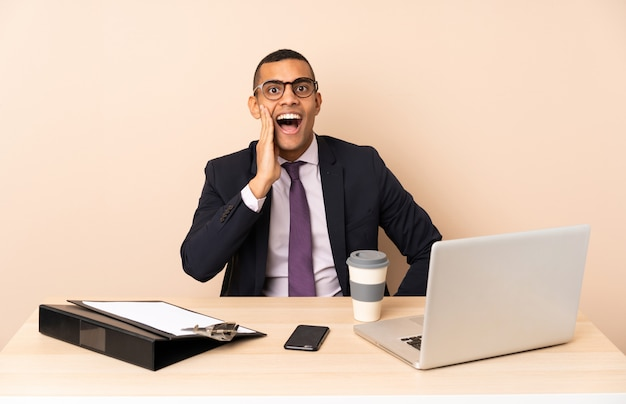 Jeune homme d'affaires dans son bureau avec un ordinateur portable et d'autres documents avec une expression faciale surprise et choquée