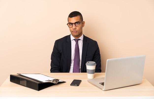 Jeune homme d'affaires dans son bureau avec un ordinateur portable et d'autres documents avec une expression triste et déprimée