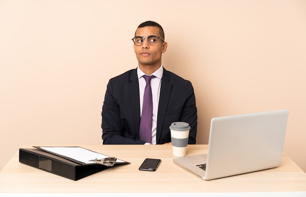 Jeune homme d'affaires dans son bureau avec un ordinateur portable et d'autres documents faisant des doutes geste regardant côté