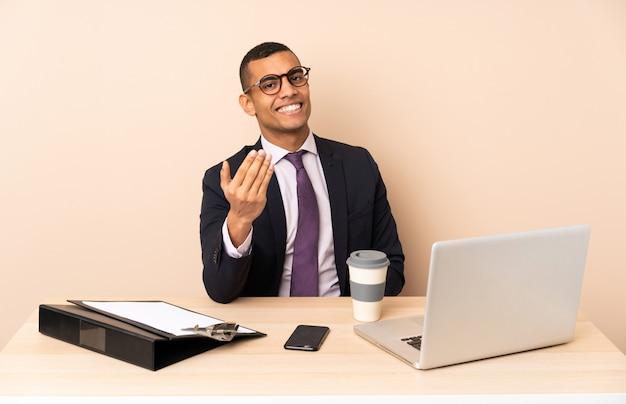 Jeune homme d'affaires dans son bureau avec un ordinateur portable et d'autres documents invitant à venir avec la main. heureux que tu sois venu
