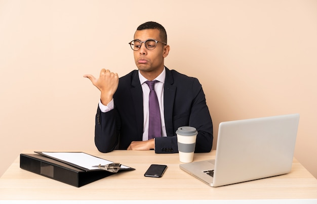 Jeune homme d'affaires dans son bureau avec un ordinateur portable et d'autres documents malheureux et pointant vers le côté