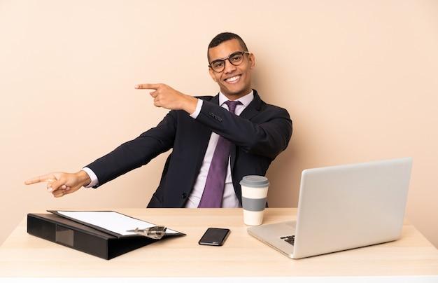 Jeune homme d'affaires dans son bureau avec un ordinateur portable et d'autres documents pointant le doigt sur le côté et présentant un produit