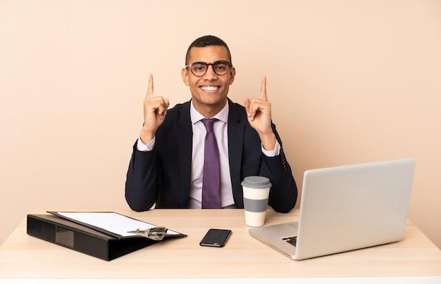 Jeune homme d'affaires dans son bureau avec un ordinateur portable et d'autres documents pointant vers le haut une excellente idée