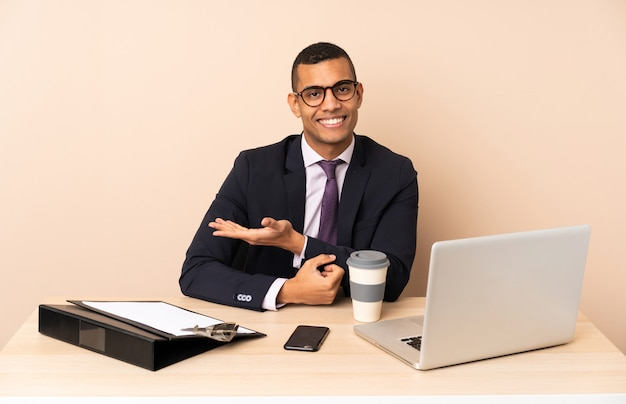 Jeune homme d'affaires dans son bureau avec un ordinateur portable et d'autres documents présentant une idée tout en regardant vers