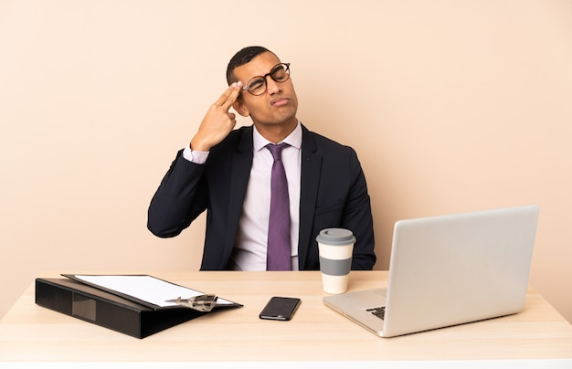 Jeune homme d'affaires dans son bureau avec un ordinateur portable et d'autres documents avec des problèmes de geste de suicide