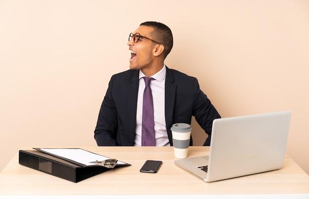 Jeune homme d'affaires dans son bureau avec un ordinateur portable et d'autres documents riant en position latérale