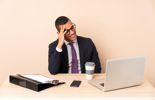 Jeune homme d'affaires dans son bureau avec un ordinateur portable et d'autres documents en riant