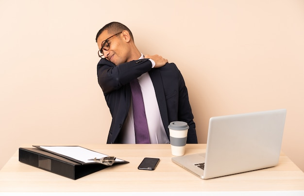Jeune homme d'affaires dans son bureau avec un ordinateur portable et d'autres documents souffrant de douleur à l'épaule pour avoir fait un effort