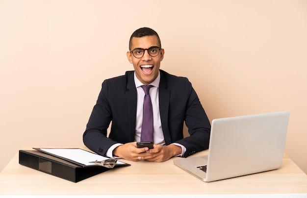 Jeune homme d'affaires dans son bureau avec un ordinateur portable et d'autres documents surpris et en envoyant un message