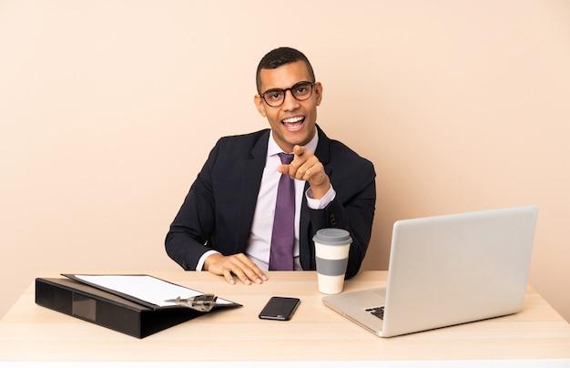 Jeune homme d'affaires dans son bureau avec un ordinateur portable et d'autres documents surpris et pointant vers l'avant
