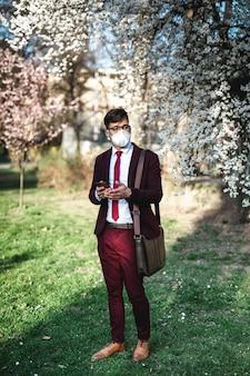 Jeune homme d'affaires debout dans un parc, utilisant un téléphone et portant un masque de protection. soins de santé, protection contre les virus, concept de protection contre les allergies.