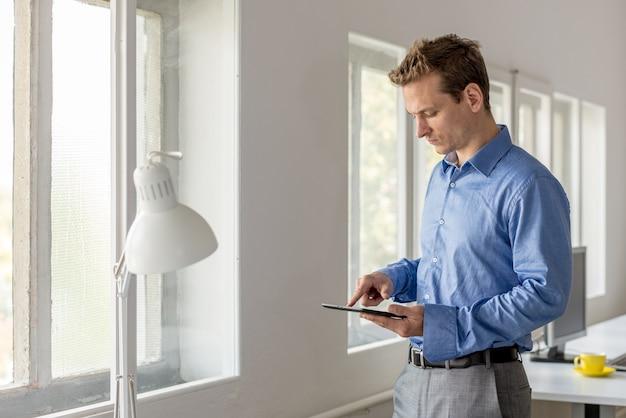 Jeune homme d'affaires debout près de la fenêtre de son bureau naviguant sur internet à l'aide de sa tablette numérique.
