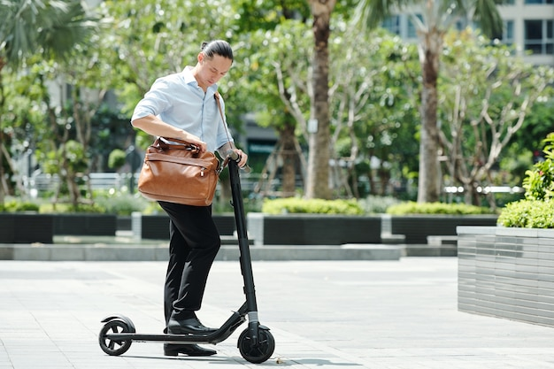 Jeune homme d'affaires debout sur scooter et vérification du document dans son sac en cuir