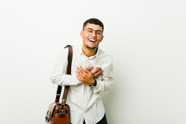 Jeune homme d'affaires décontracté hispanique rire en gardant les mains sur le cœur, le concept du bonheur.