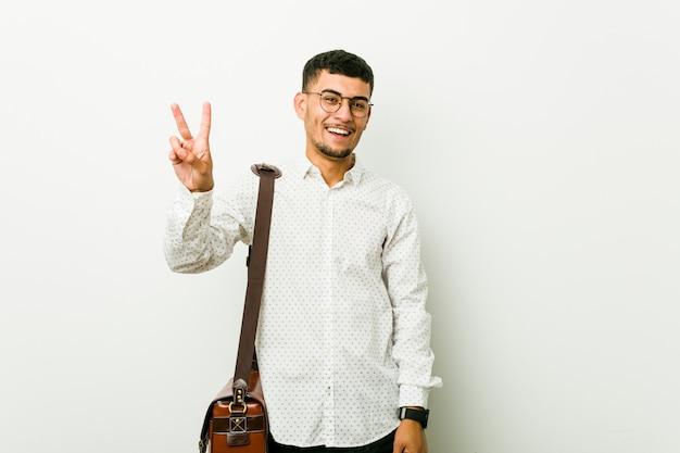 Jeune homme d'affaires décontractée joyeuse et insouciante montrant un symbole de la paix avec les doigts