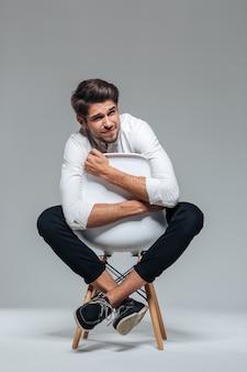 Jeune homme d'affaires déprimé dans la douleur assis sur la chaise isolée sur un mur gris