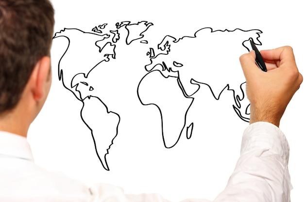 Un jeune homme d'affaires dessinant une carte du monde