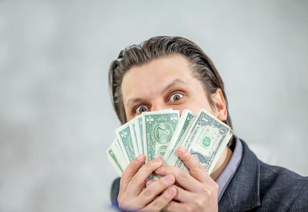 Jeune homme d'affaires détenant de l'argent comptant - le concept de succès et de joie