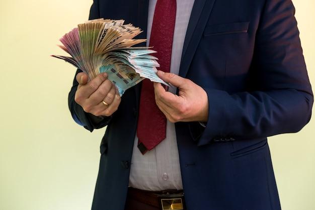 Jeune homme d'affaires détenant une énorme somme d'argent. nouveaux billets ukrainiens uah 1000 et 500 entre les mains d'un homme d'affaires. profit.