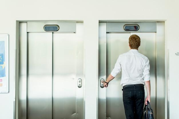 Jeune homme d'affaires devant l'ascenseur
