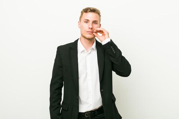 Jeune homme d'affaires avec les doigts sur les lèvres en gardant un secret
