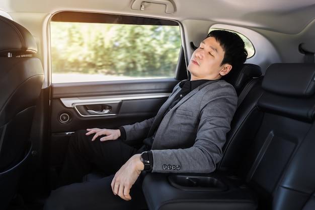 Jeune homme d'affaires dormant assis sur le siège arrière de la voiture