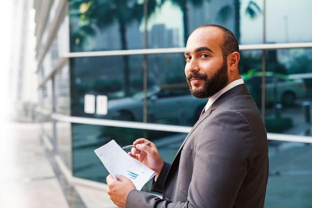 Jeune homme d'affaires du moyen-orient lisant des rapports de fonds