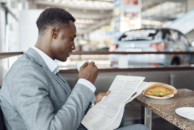 Jeune homme d'affaires ébène avec journal en train de déjeuner au café de bureau. homme d'affaires prospère boit du café dans l'aire de restauration, homme noir en tenue de soirée