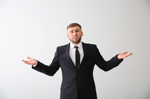 Jeune homme d'affaires émotionnel après avoir fait une erreur sur fond blanc