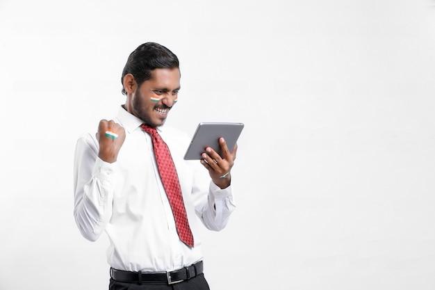 Jeune homme d'affaires ou employé indien utilisant un smartphone.