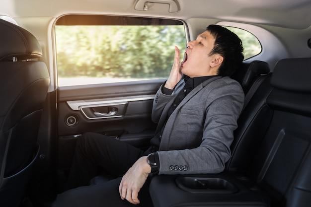 Jeune homme d'affaires endormi bâillant alors qu'il était assis sur le siège arrière de la voiture