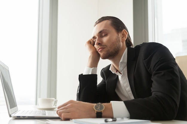Jeune homme d'affaires endormi devant un ordinateur portable au travail.